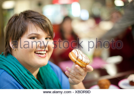Portrait of young woman holding doughnut - Stock Photo