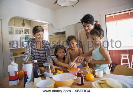 Family preparing breakfast in kitchen - Stock Photo