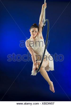 Aerialist poised on hoop against blue background - Stock Photo