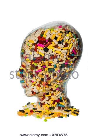 Kopf aus Glas mit Tabletten gefuellt. Symbolphoto fuer Medikamente, Tablettenmissbrauch und Tablettensucht | head filled with pi - Stock Photo