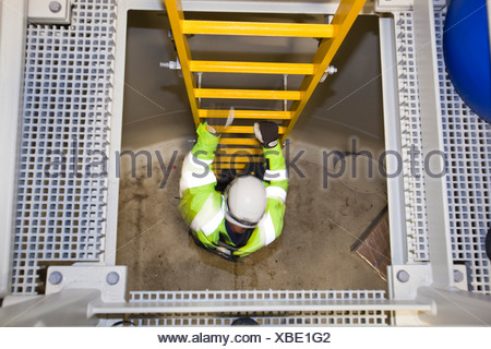 An engineer descends into the base of a transition piece on a wind turbine at the Walney offshore wind farm. - Stock Photo