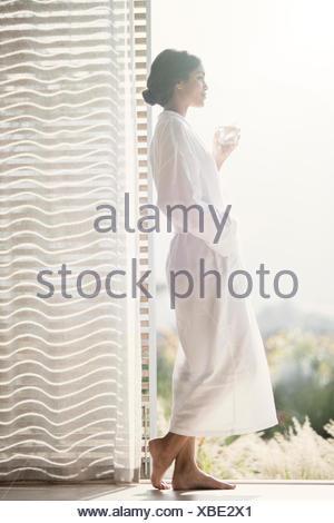 Woman in bathrobe drinking water at open door - Stock Photo