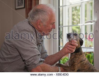 Senior man stroking pet dog - Stock Photo