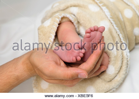 Father's hand holding feet of newborn baby - Stock Photo