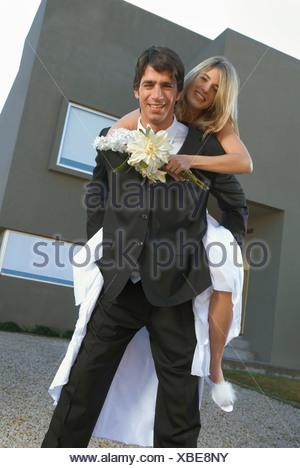 Groom giving bride piggyback ride - Stock Photo