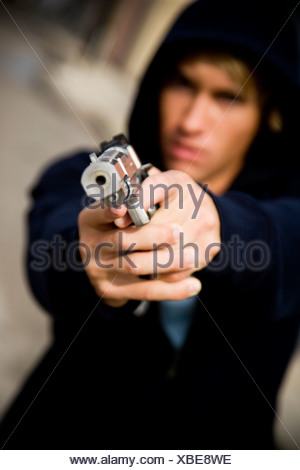 Portrait of a young man holding a gun - Stock Photo