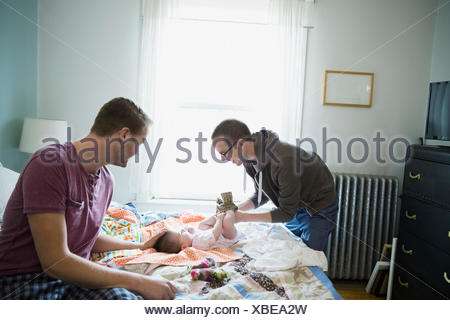 Homosexual couple playing with baby on bed - Stock Photo