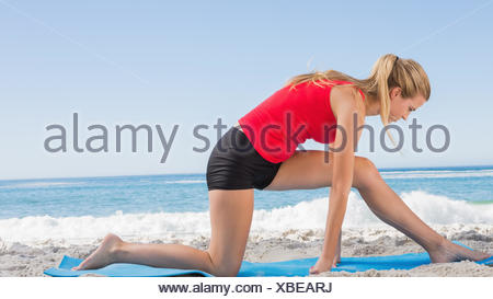 Fit blonde stretching leg on exercise mat - Stock Photo