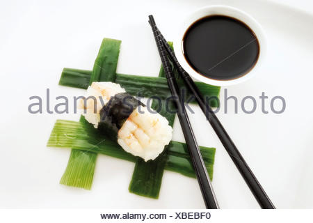Sushi Nigiri, made with shrimp and rice wrapped in nori seaweed and placed beside black chopsticks and a bowl of soy sauce on - Stock Photo