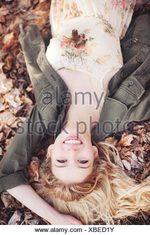 Woman lying on autumn leaves - Stock Photo