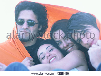 Friends wrapped in orange blanket, close-up - Stock Photo