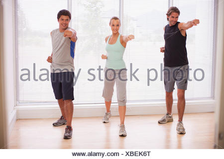 Portrait of smiling people in yoga class - Stock Photo