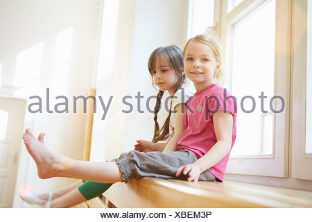 Girls sitting on apparatus in school hall - Stock Photo