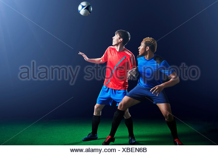 Male soccer players with ball mid air - Stock Photo