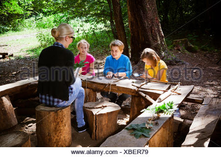 Children and teacher crafting in forest camp, Munich, Bavaria, Germany - Stock Photo