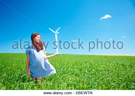Girl on field with wind turbine - Stock Photo