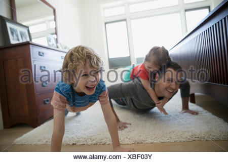 Father and children doing push-ups bedroom rug - Stock Photo