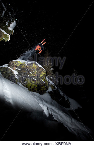 A male telemark skier front flips off a cliff at night in Montana. - Stock Photo