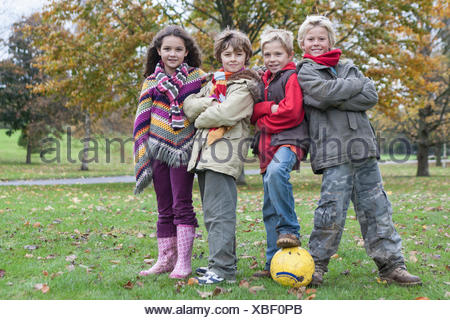 Portrait of four children with football in park - Stock Photo