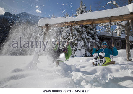 Germany, Bavaria, Inzell, couple having fun on swings in snow-covered landscape - Stock Photo