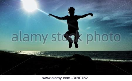 Boy Jumping Into Air Against Sun - Stock Photo