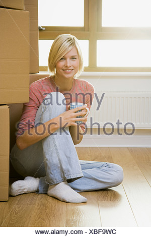 Woman taking a break from moving in - Stock Photo
