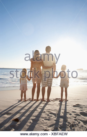 Family on beach holding hands - Stock Photo