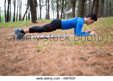 Athlete exercising planks in forest - Stock Photo
