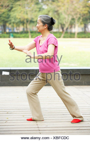 Senior Chinese Woman Doing Tai Chi In Park - Stock Photo