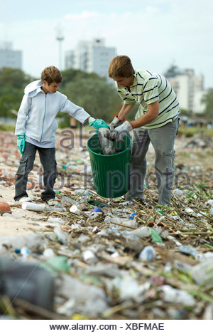 Two people in garbage dump, collecting recyclable plastic materials in garbage can - Stock Photo