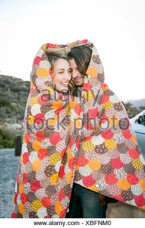 Young couple wrapped in patchwork blanket smiling - Stock Photo