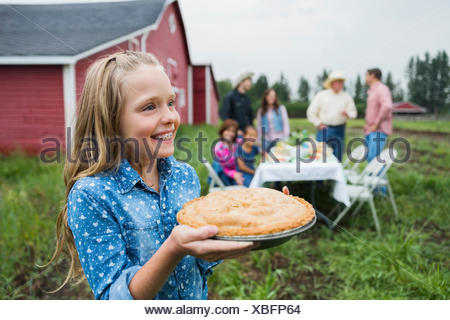 Smiling girl carrying pie outside barn - Stock Photo