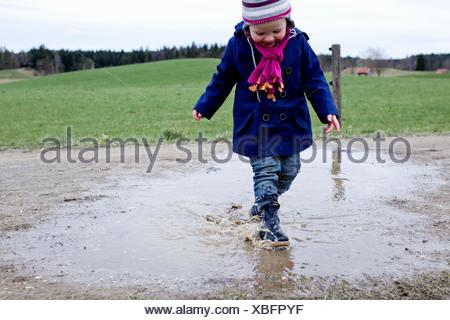 Female toddler wearing rubber boots splashing in puddle - Stock Photo