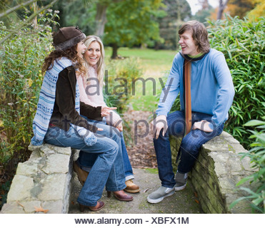 Man and two women outdoors sitting on stone wall - Stock Photo