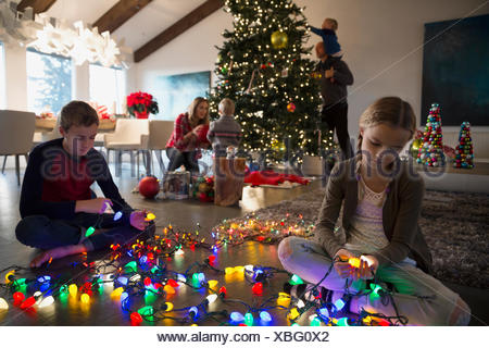 Brother and sister untangling Christmas tree string lights - Stock Photo