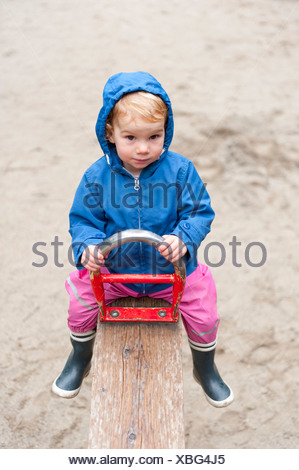 Girl, 18 months, sitting on a seesaw at a playground wearing rain protection, Munich, Upper Bavaria, Bavaria - Stock Photo
