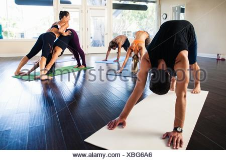 Yoga instructor helping woman in class - Stock Photo