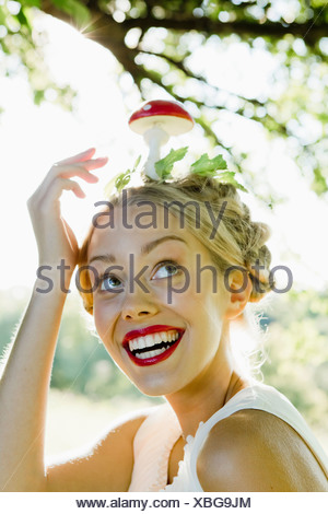 Woman balancing mushroom on her head - Stock Photo