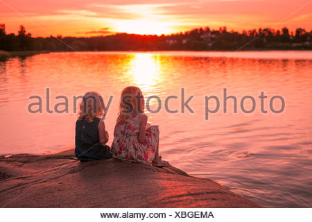 Rear view of two girls sitting on rocks by the sea at sunset - Stock Photo