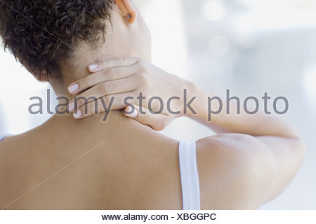 Woman rubbing sore neck - Stock Photo