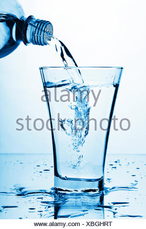 pure water splashing from bottle into glass - Stock Photo