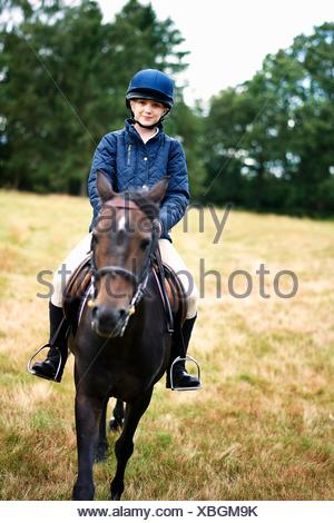 Portrait of girl horseback riding in field - Stock Photo