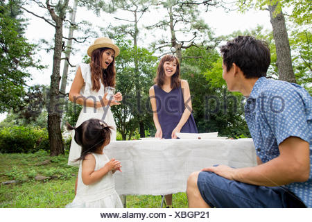 Group of friends at an outdoor party in a forest. - Stock Photo