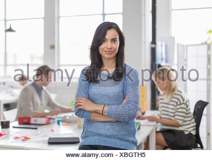 Mid adult woman sitting on desk and smiling in creative office, portrait - Stock Photo