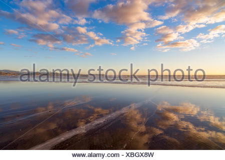Cloudy sky reflected in sea - Stock Photo