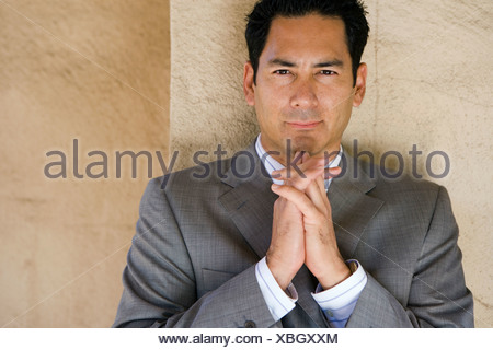 Businessman in grey suit standing with hands clasped together smiling front view portrait - Stock Photo