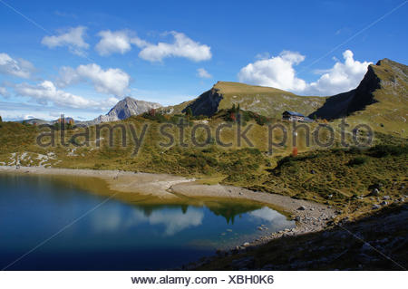 Unterwegs in den Tannheimer Bergen in Tirol, Oesterreich; Blick auf eine Berghütte und die Grüne Lache; der kleine Bergsee ist von kahlen Bergen umgeben; sonniger Tag im Herbst mit blauen Himmel und weißen Wolken Heading into the Tannheim Mountains in Tyrol, Austria; view on a mountain hut and the Gruene Lache; the small lake is surrounded by barren mountains, sunny autumn day with blue sky and white clouds - Stock Photo