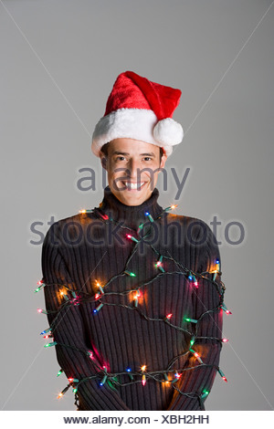 Man tied up in christmas lights - Stock Photo
