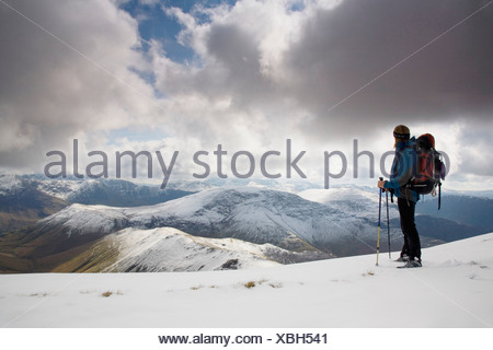 Hiker overlooking snow covered Newlands Valley - Stock Photo