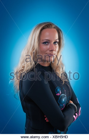 Young woman wearing a wetsuit and impact vest, equipment for wakeboarding craze - Stock Photo